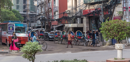 Rickshaw drivers waiting on a street corner