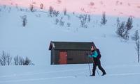 Skiing past Trollvassbu at sunset