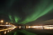 Northern lights dancing over the bridge to Håkøya